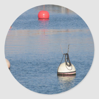 Lots of mooring buoys floating on calm sea water classic round sticker