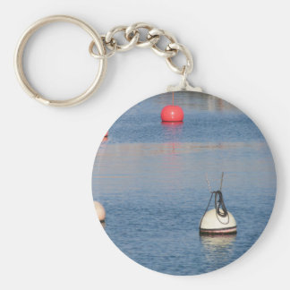 Lots of mooring buoys floating on calm sea water keychain
