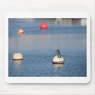 Lots of mooring buoys floating on calm sea water mouse pad