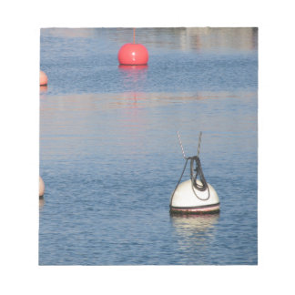 Lots of mooring buoys floating on calm sea water notepad