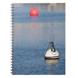 Lots of mooring buoys floating on calm sea water spiral notebook