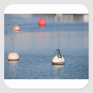 Lots of mooring buoys floating on calm sea water square sticker