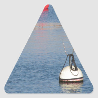 Lots of mooring buoys floating on calm sea water triangle sticker