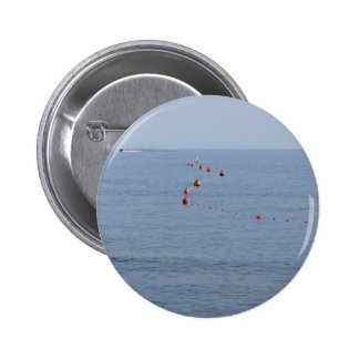 Lots of mooring buoys floating on water in marina 2 inch round button