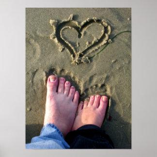 Lovebirds make heart in sand by ocean in poster