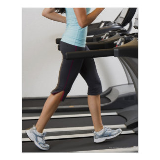 Low section of woman walking on treadmill poster