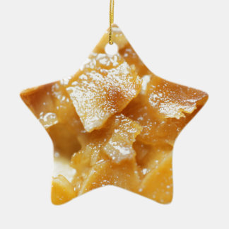 Macro of almond splitters on a cake ceramic star ornament