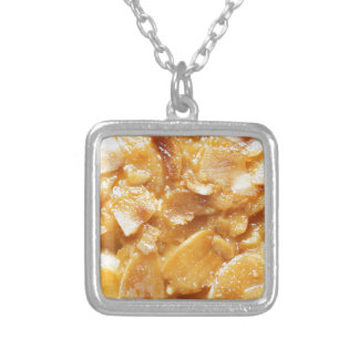 Macro of almond splitters on a cake silver plated necklace