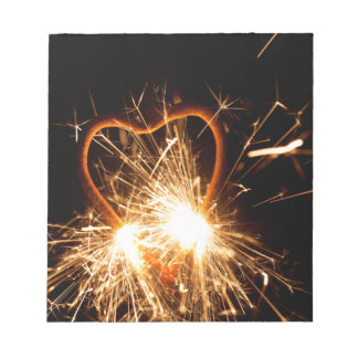 Macro photo of a burning sparkler in form of a hea notepad
