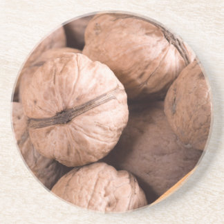 Macro view of a group of walnuts in a wooden box coaster