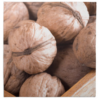 Macro view of a group of walnuts in a wooden box napkin