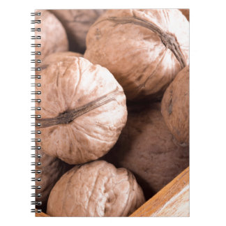 Macro view of a group of walnuts in a wooden box notebook