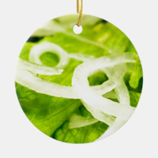 Macro view of the leaves of lettuce and onion ring round ceramic ornament