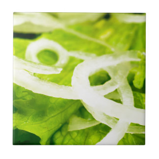 Macro view of the leaves of lettuce and onion ring tile