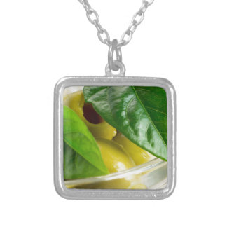 Macro view of the marinated olives with green silver plated necklace