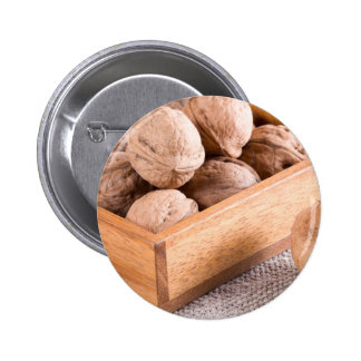 Macro view of walnuts close up in a wooden box 2 inch round button