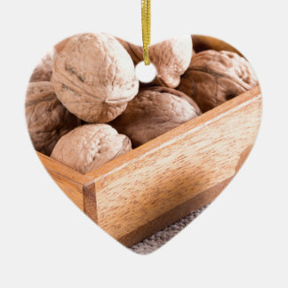 Macro view of walnuts close up in a wooden box ceramic heart ornament