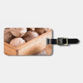 Macro view of walnuts close up in a wooden box luggage tag