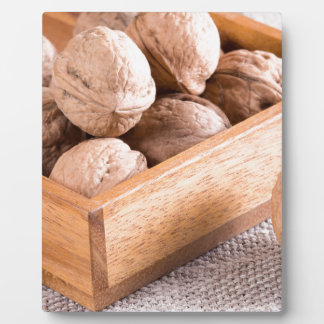 Macro view of walnuts close up in a wooden box plaque
