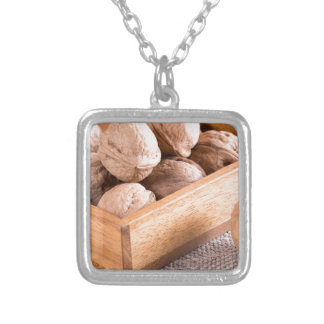Macro view of walnuts close up in a wooden box silver plated necklace