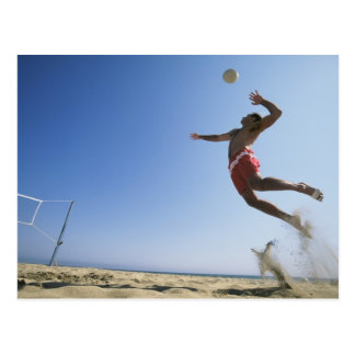 Male beach volleyball player jumping up to spike postcard