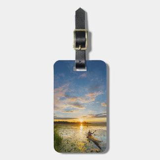 Male kayaker paddling sea kayak on still water travel bag tag
