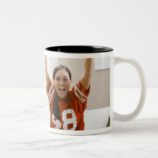 Man and woman sitting on sofa watching football Two-Tone coffee mug