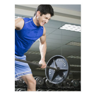 Man in gym, lifting large barbell, clenching postcard