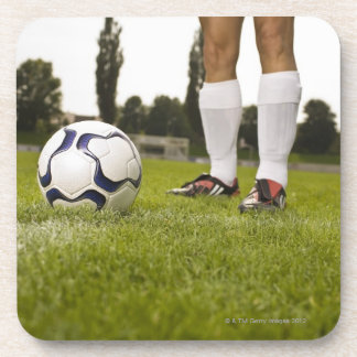 Man in soccer uniform standing with soccer ball coaster