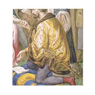 man in yellow kneels notepad