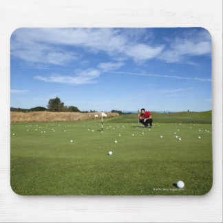 Man lining up a putt while golfing. mouse pad