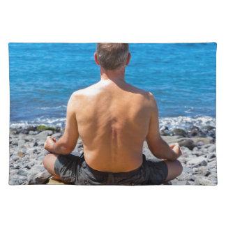 Man meditating at beach and sea placemat