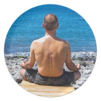 Man meditating at beach and sea plate