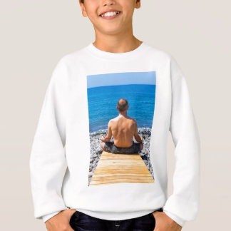 Man meditating at beach and sea sweatshirt