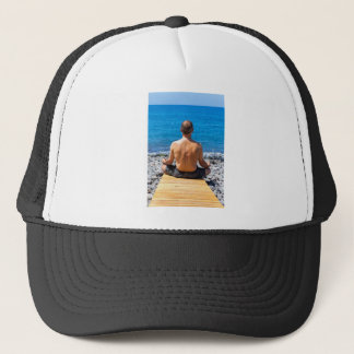Man meditating at beach and sea trucker hat