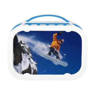 Man on a snowboard jumping off a cornice at lunch box