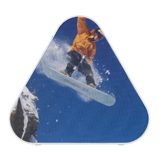 Man on a snowboard jumping off a cornice at bluetooth speaker