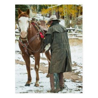 Man putting saddle on horse postcard
