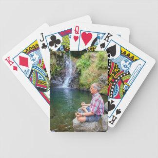 Man sitting on rock meditating near waterfall bicycle playing cards