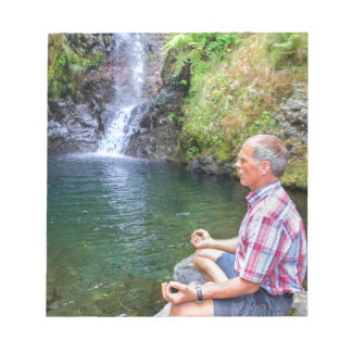 Man sitting on rock meditating near waterfall notepad