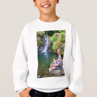 Man sitting on rock meditating near waterfall sweatshirt
