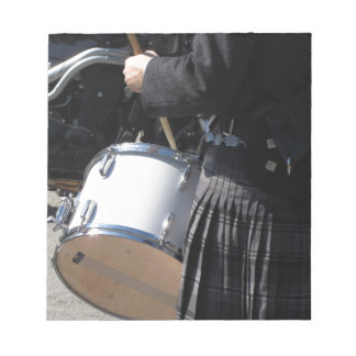 Man with kilt playing on drums notepad