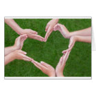 Many arms of children construct heart above grass card
