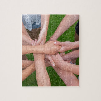 Many arms of children holding hands together jigsaw puzzle