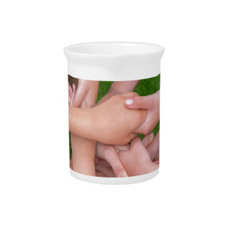 Many arms of children holding hands together pitcher