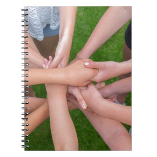 Many arms of children holding hands together spiral notebook