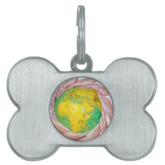 Many arms of children with hands holding globe pet name tag