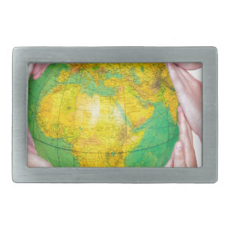 Many arms of children with hands holding globe rectangular belt buckles