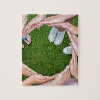 Many arms of children with hands making circle jigsaw puzzle