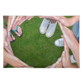 Many arms of children with hands making circle placemat